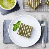 Matcha zielonej herbaty punktu tort z białą czekoladą na białego talerza Popielatym kamiennym tle Zdjęcie Royalty Free