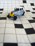 Matchbox car. Image of a toy car placed on crossword puzzle Stock Image