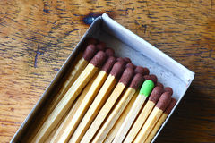 Matchbox with a different match. Matchbox of brown matches with a green one. This image can be used as metaphore of a good idea. In a matchbox there are many Royalty Free Stock Images