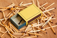 Matchbox lying on pile of matches. Yellow matchbox lying on pile of matches on a wooden surface royalty free stock photography