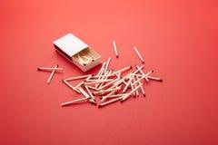 Matchbox nad czerwonym tłem Fotografia Stock