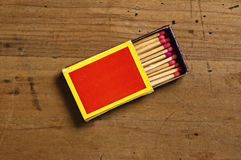 Matchbox on table. Overhead view of open matchbox and matches on old wooden table Stock Photo