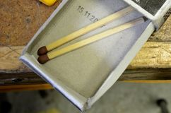 Matchbox with two matches on wooden workbench Stock Photo
