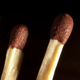 Matches. Detail of two matches against a dark background royalty free stock images