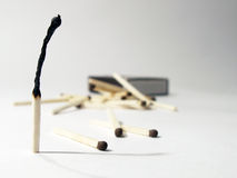 Matches. Burnt match standing on background with lying matches and match-box Stock Image