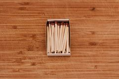 Matches in a box. Small wooden matches in a box on the wooden board. Closeup photography Royalty Free Stock Photos