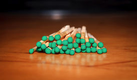 Matches with green head. On a wooden background Stock Photo