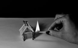 Matches house and hand with burning fire - risk of accident Royalty Free Stock Photography