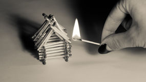 Matches house and hand with burning fire - risk of accident Stock Photos