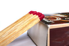 Matches lie against a matchbox, macro shot. Royalty Free Stock Image