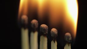 Matches light up one by another in series on black background. Slow motion and time lapse stock video footage
