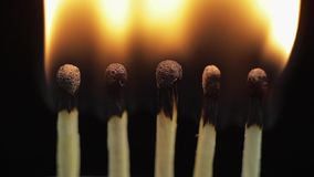 Matches light up one by another in series on black background. Slow motion and time lapse stock footage