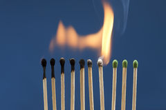 Matches lit in chain reaction. Royalty Free Stock Photo
