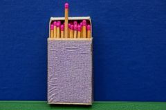 An open box with matches on a blue background Royalty Free Stock Photos