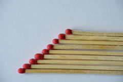 Matches in row. With red heads on white Royalty Free Stock Photo