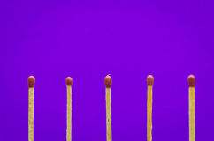 Matches setting on purple  background for ideas and inspiration Royalty Free Stock Image