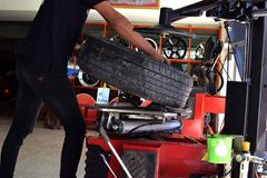 Matchine de commutateur de pneu d'utilisation de travailleur dans la boutique de voiture de pneu image libre de droits