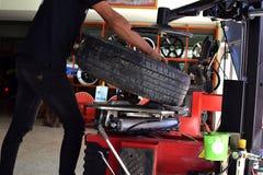 Matchinen för changer för arbetarbruksgummihjul i gummihjulbil shoppar royaltyfri bild