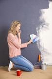 Matching the best color. Full length shot of a woman matching color while painting wall at home stock images