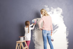 Matching the best colors. Rear view sho of a casual women and her cute daugther painting the wall and matching colours together in the living room stock photos