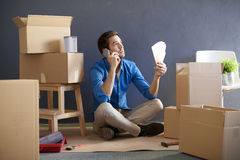 Matching colors. Full length shot of a young man surrounded by cardboard box sitting in room and matching wall color after moving a new flat Stock Photo