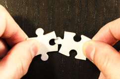 Matching. First matching of a two pieces white jigsaw/puzzle whit one gap, over  black wooden table background, symbol of problem solving Royalty Free Stock Photos