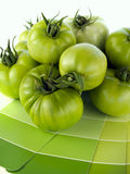 Matching green paint colors to nature. Green tomatoes with matching green paint color swatches stock photos