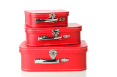 Matching Luggage. A set of matching luggage pieces stacked on top of each other. Three different sizes of red suitcase isolated on white with a slight reflection Royalty Free Stock Photo