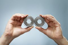 Matching Pair. A Man holding a matching pair of old cog gear wheels in his hands stock images
