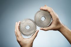 Matching pair. Man holding a pair of old metallic cog gear wheels in his hands royalty free stock photo