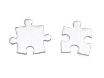 Matching puzzle pieces. Two silver matching puzzle pieces over white background stock photo