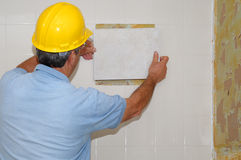 Matching tiles. Man with safety hat matching tiles on a wall Stock Image