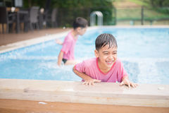 Matching top boys love to be in the water. Little sibling boy playing in swimming pool Stock Photography
