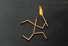 Matchpinnespring med brand på huvudet Arkivbild