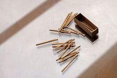 Matchstick and matchbox. White matchstick and matchbox on wooden table Stock Image