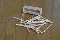 Matchstick and matchbox. White matchstick and matchbox on wooden table Royalty Free Stock Images