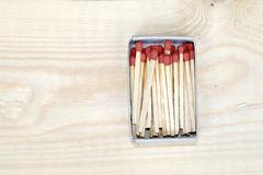 Matchstick in matchbox on wooden background Royalty Free Stock Image