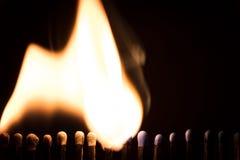 Matchsticks bränner framme av svart, avfyrar och flammor fotografering för bildbyråer