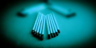 Matchsticks fijados en la foto común del fondo azul fotografía de archivo