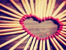Matchsticks in Form eines Herzens tonten mit einem warmen Retro- Weinlese instagram Filtereffekt Stockfotos