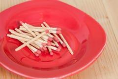 Matchsticks i röd platta över trä Royaltyfria Foton