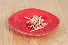 Matchsticks i röd platta över trä Arkivbild