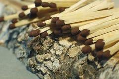 Matchsticks mit braunen Tipps auf einem Birkenbrettmakroabschluß oben Stockfoto
