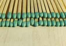 Matchsticks mit grünen Tipps auf einem Birkenbrettmakroabschluß oben Lizenzfreie Stockfotos