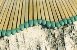 Matchsticks mit grünen Tipps auf einem Birkenbrettmakroabschluß oben Stockbild