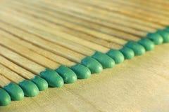 Matchsticks mit grünen Tipps auf einem Birkenbrettmakroabschluß oben Stockfotografie