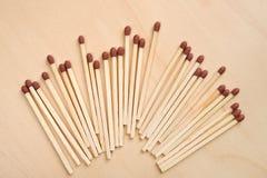Matchsticks op een rij op houten lijst stock afbeelding