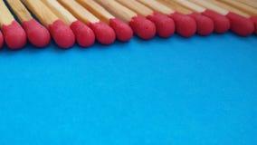 Matchsticks op een rij over blauwe achtergrond stock foto's