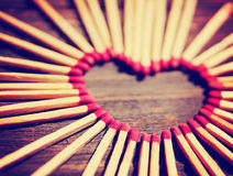 Matchsticks in the shape of a heart toned with a warm retro vintage instagram filter effect Stock Photos