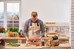 Mate sostener el pedazo sólido de carne del filete del cerdo en cocina con el fondo de las verduras imagen de archivo